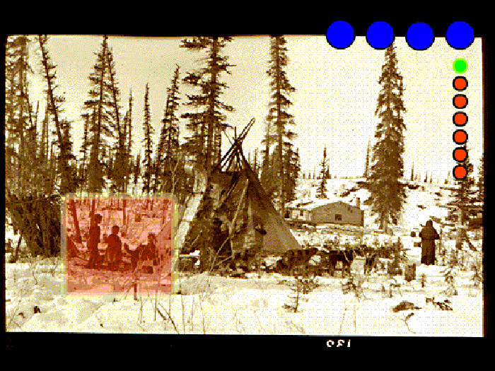 Archival photo of native children in front of winter tipi with cabin n background, coloured dots superimposed