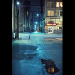 Blurry time exposure of woman walking past alley along Vancouver's Hastings Street, wet pavement night shot