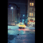 Blurry shot of yellow taxi pulling out of alley onto Vancouver's Hastings Street, wet pavement night shot